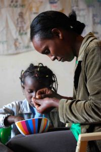 A great joy of the day was watching kids like Wanja enjoying the process of creating with caregivers like SoH #2 cook, Flo