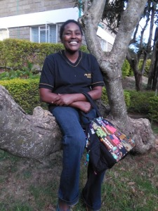 Joyce, with a bag created by Tuungane Pamoja, 2015.